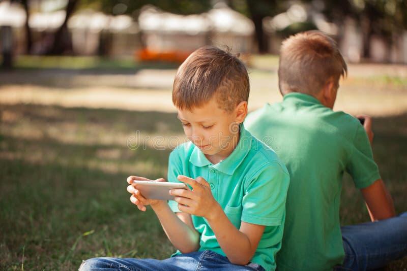 Aanbiddelijke jongenszitting op het gras in het park en het spelen met smartphone Kind die leren hoe te smartphone te gebruiken royalty-vrije stock afbeelding