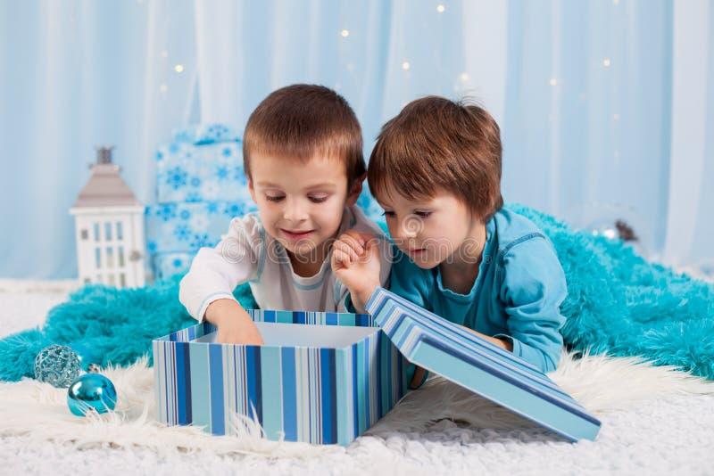 Aanbiddelijke kinderen, jongensbroers, die met Kerstmisdecorati spelen stock afbeeldingen