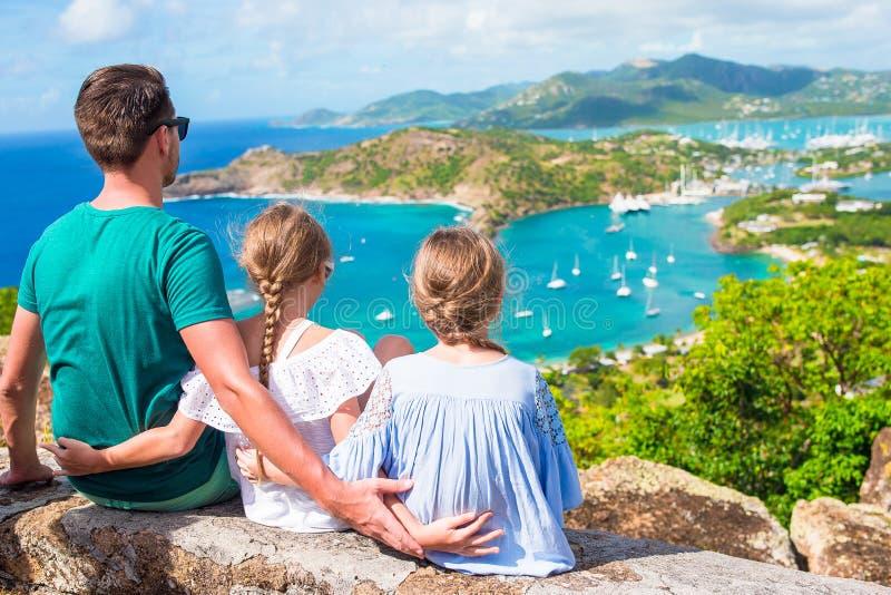 Aanbiddelijke kleine jonge geitjes en jonge vader die van de mening van schilderachtige Engelse Haven genieten bij Antigua in Car stock foto