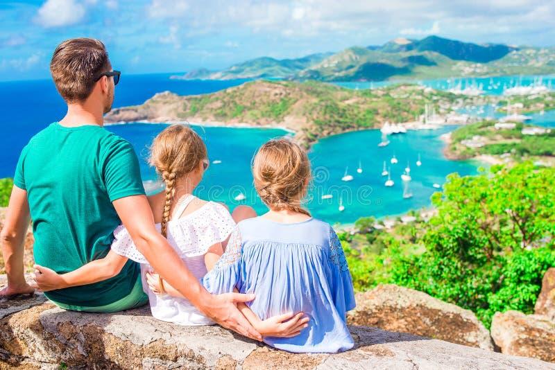 Aanbiddelijke kleine jonge geitjes en jonge vader die van de mening van schilderachtige Engelse Haven genieten bij Antigua in Car royalty-vrije stock fotografie