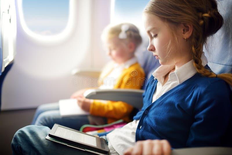 Aanbiddelijke kleine kinderen die door een vliegtuig reizen Meisjeszitting door vliegtuigenvenster en lezing haar ebook tijdens d royalty-vrije stock afbeeldingen