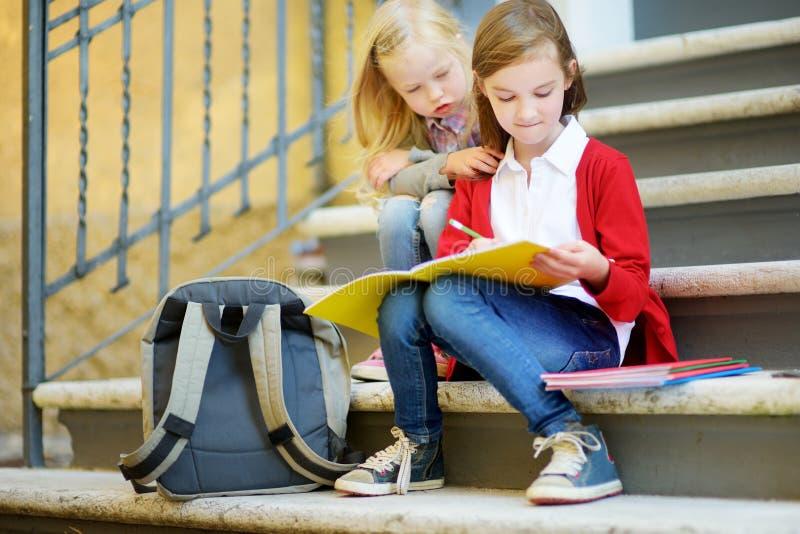 Aanbiddelijke kleine schoolmeisjes die in openlucht op heldere de herfstdag bestuderen Jonge studenten die hun thuiswerk doen Ond royalty-vrije stock afbeelding