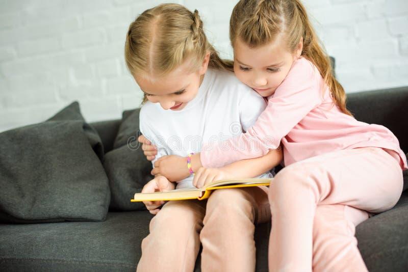 aanbiddelijke kleine zusters die boek samen op bank lezen stock afbeelding