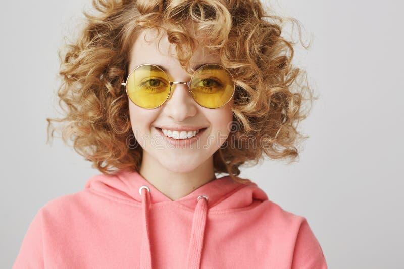 Aanbiddelijke krullend-haired vrouw die met modieuze gele zonnebril bij camera over grijze achtergrond glimlachen Leuke kunstenaa stock afbeelding