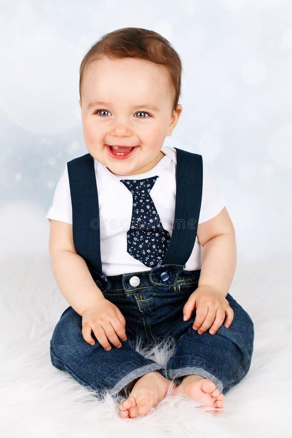 Aanbiddelijke lachende baby met steunen en band stock foto
