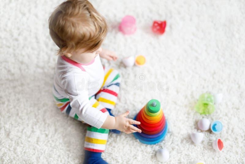 Aanbiddelijke leuk mooi weinig babymeisje die met onderwijs kleurrijke houten rainboy stuk speelgoed piramide spelen stock fotografie