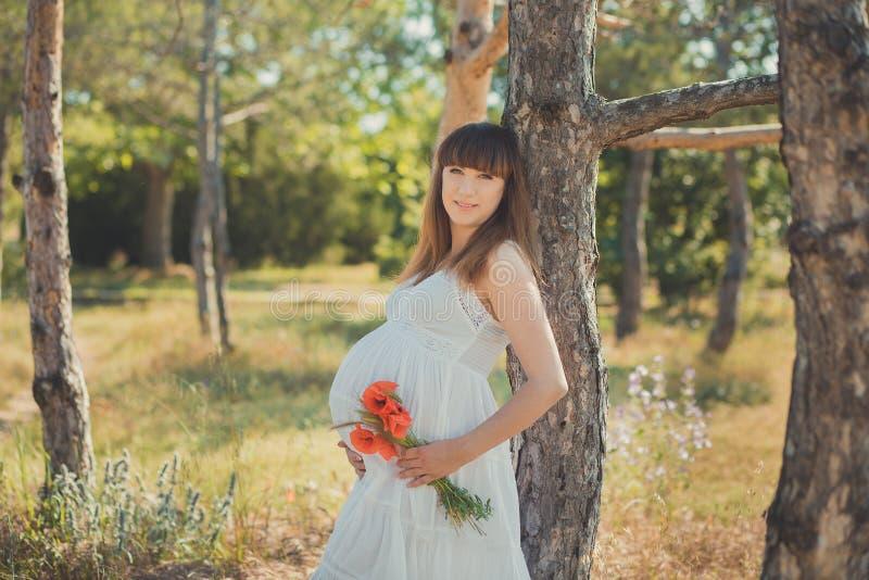 Aanbiddelijke leuke zwangere damevrouw in het witte luchtige kleding stellen dicht bij boom in het bos de buik van de holdingsbui stock foto