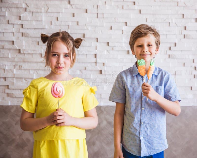 Aanbiddelijke meisje en jongen die kleurrijke zoete schuimgebakjes op een stok op Pasen-dag houden royalty-vrije stock fotografie