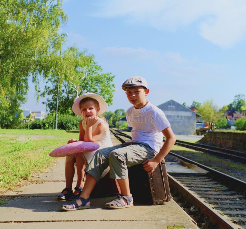 Aanbiddelijke meisje en jongen op een station, die op de trein met uitstekende koffers wachten Het reizen, vakantie en royalty-vrije stock afbeeldingen