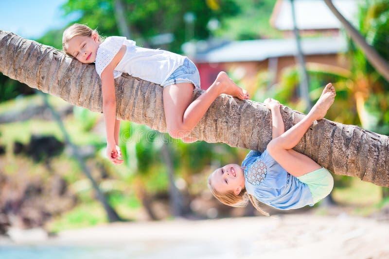 Aanbiddelijke meisjes bij tropisch strand die pret op palm hebben tijdens de zomervakantie De jonge geitjes genieten van hun vaka royalty-vrije stock afbeelding