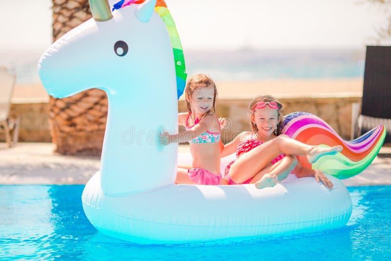 Aanbiddelijke meisjes bij zwembad die pret hebben tijdens de zomervakantie royalty-vrije stock afbeelding