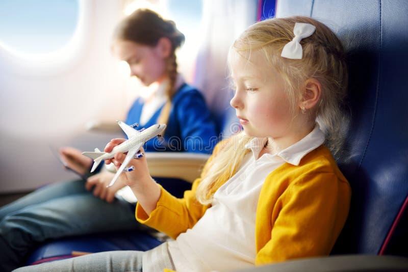 Aanbiddelijke meisjes die door een vliegtuig reizen Kinderen die door vliegtuigenvenster zitten en met stuk speelgoed vliegtuig s royalty-vrije stock foto