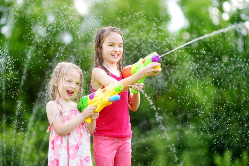 Aanbiddelijke meisjes die met waterkanonnen spelen op hete de zomerdag Leuke kinderen die pret met water hebben in openlucht stock foto