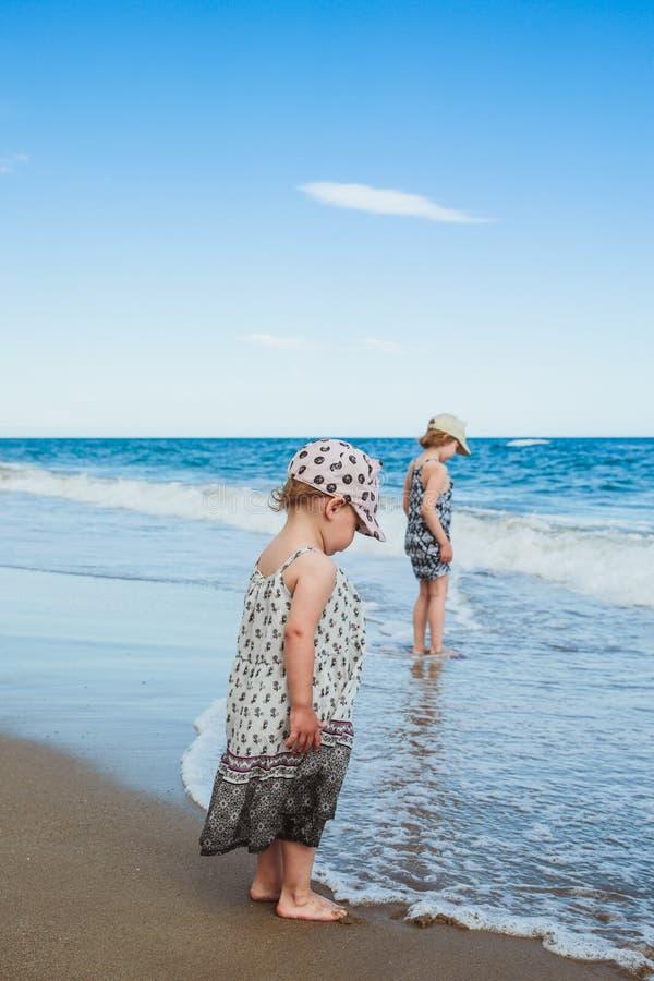 Aanbiddelijke meisjes die op het water op het strand lopen royalty-vrije stock foto