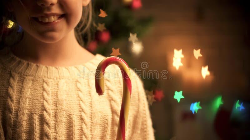 Aanbiddelijke meisjes glimlachende holding in riet van het handen het zoete suikergoed, Kerstmisvakantie royalty-vrije stock foto's