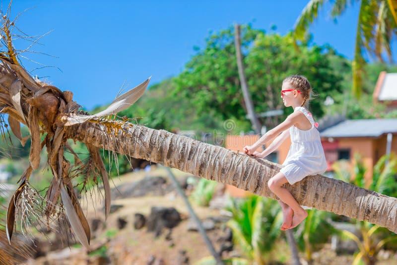 Aanbiddelijke meisjezitting op palm tijdens de zomervakantie op wit strand stock fotografie