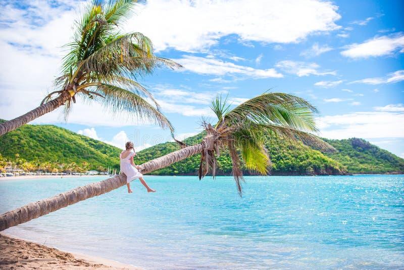 Aanbiddelijke meisjezitting op palm tijdens de zomervakantie op wit strand royalty-vrije stock afbeelding