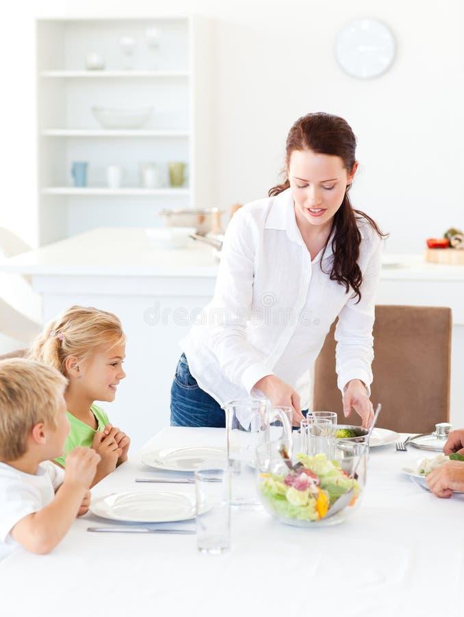 Aanbiddelijke moeder dienende salade aan haar kinderen stock afbeeldingen