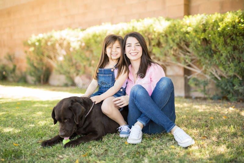Aanbiddelijke moederdochter met hond royalty-vrije stock foto