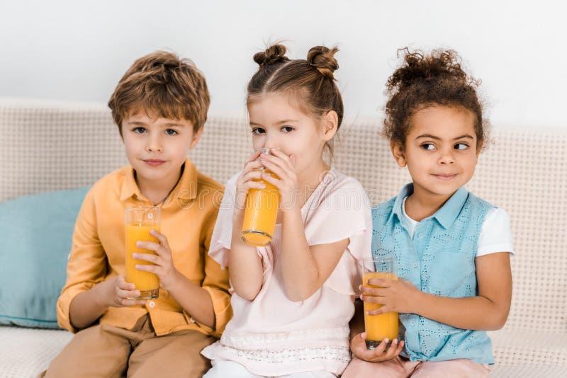aanbiddelijke multi-etnische kinderen die samen zitten en stock fotografie