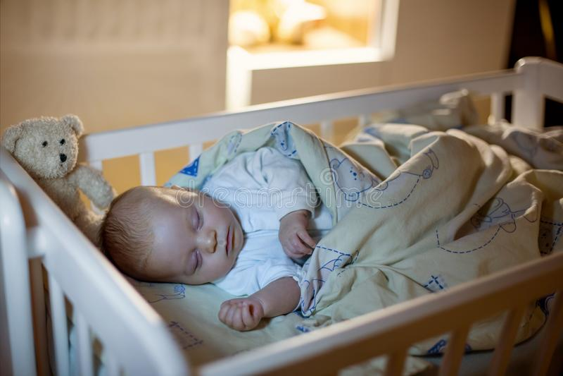 Aanbiddelijke pasgeboren babyjongen, die in voederbak bij nacht slapen royalty-vrije stock foto