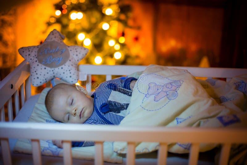 Aanbiddelijke pasgeboren babyjongen, die in voederbak bij nacht slapen royalty-vrije stock fotografie