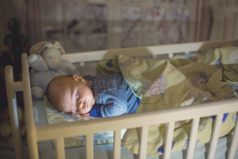 Aanbiddelijke pasgeboren babyjongen, die in voederbak bij nacht slapen stock foto