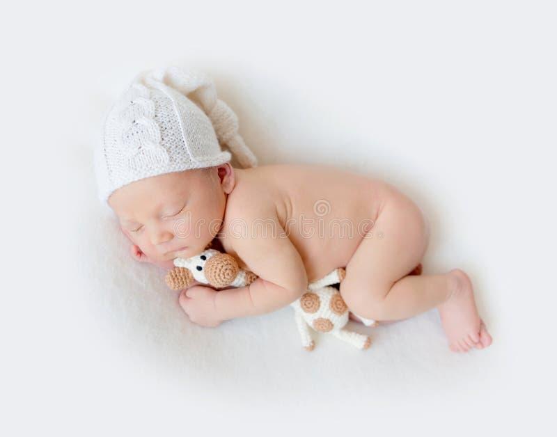 Aanbiddelijke pasgeboren babyslaap die een stuk speelgoed houden stock fotografie