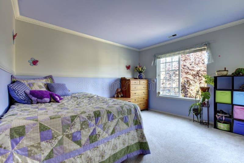 Aanbiddelijke purpere jonge geitjesruimte met eenvoudige en comfortabele interioir royalty-vrije stock foto