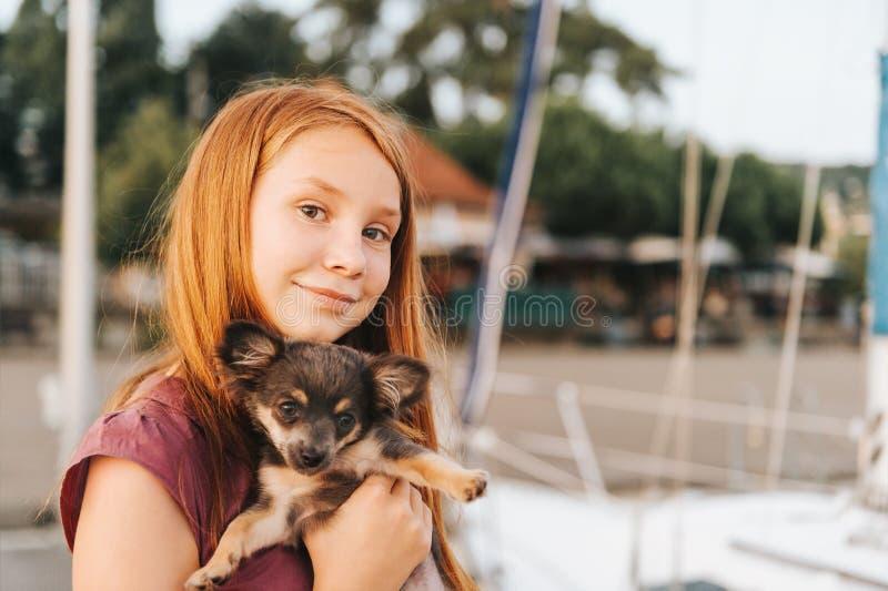 Aanbiddelijke roodharige het puppychihuahua van de meisjesholding royalty-vrije stock afbeelding