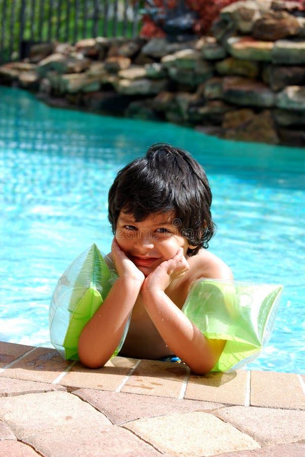 Aanbiddelijke Spaanse jongen door de pool stock fotografie