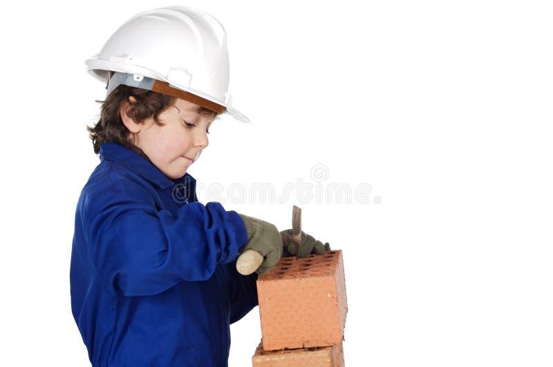 Aanbiddelijke toekomstige bouwer die een bakstenen muur construeert stock fotografie
