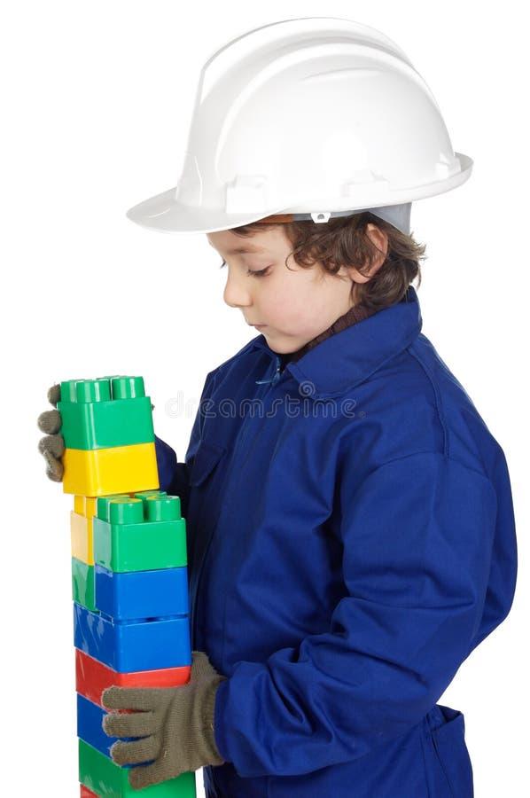Aanbiddelijke toekomstige bouwer die een bakstenen muur met stuk speelgoed stuk construeert stock foto