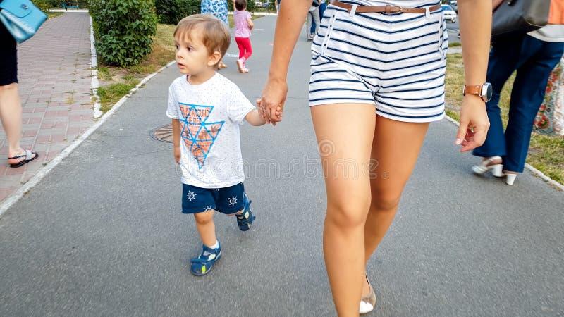 Aanbiddelijke 3 van de oude peuterjaar jongen die zijn moeder houden met de hand en op straat lopen royalty-vrije stock afbeelding
