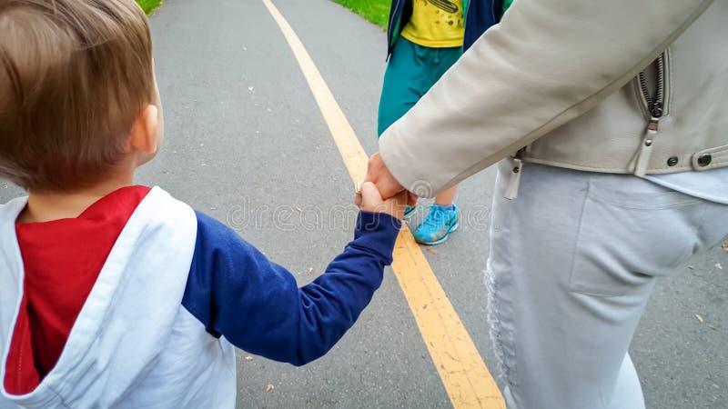 Aanbiddelijke 3 van de oude peuterjaar jongen die zijn moeder houden met de hand en op straat lopen stock foto's