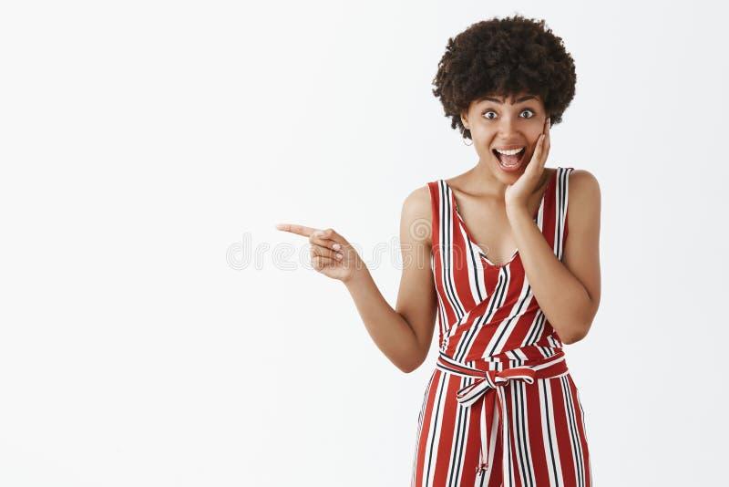 Aanbiddelijke verbaasde en geïmponeerde aantrekkelijke Afrikaanse Amerikaanse vrouwelijke student in modieuze formele gestreepte  stock fotografie