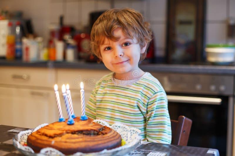 Aanbiddelijke vier éénjarigenjongen die zijn verjaardag en het blazen vieren stock foto