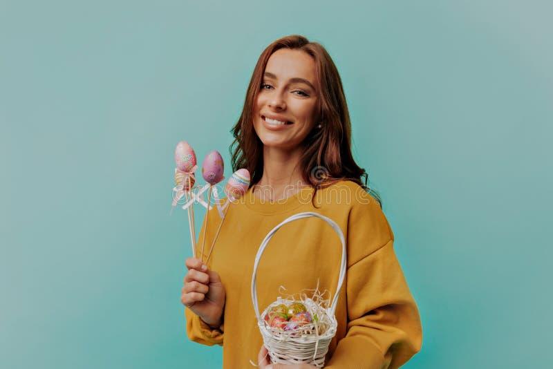 Aanbiddelijke volwassen jonge vrouw die heldere kleren op Pasen-dag dragen De mand van de vrouwenholding met geschilderde eieren stock afbeeldingen