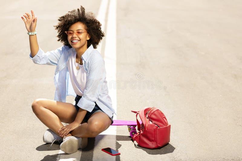 Aanbiddelijke vrouw die bij vriend golven terwijl het zitten op skateboard stock afbeelding