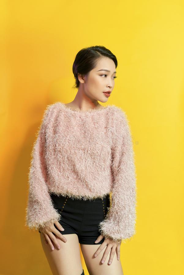 Aanbiddelijke vrouw die ware positieve emoties uitdrukken tijdens photoshoot in roze bontjas Binnenportret van actief betoverend  stock fotografie
