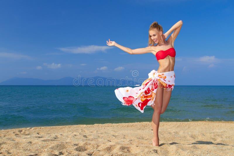 Aanbiddelijke vrouw die zich bij het tropische strand bevinden stock fotografie