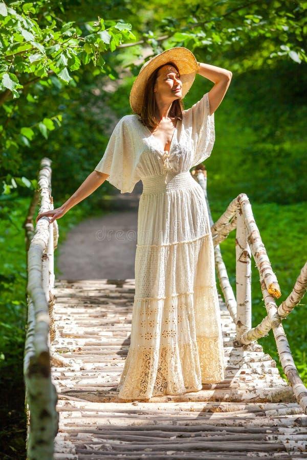 Aanbiddelijke vrouw in een witte kleding en strohoed in het oude park royalty-vrije stock afbeeldingen