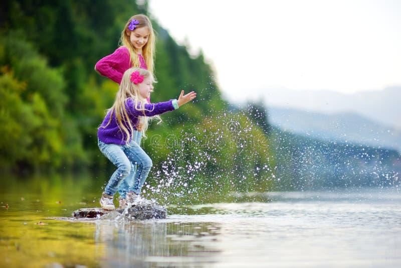 Aanbiddelijke zusters die door Hallstatter See meer in Oostenrijk op warme de zomerdag spelen De leuke kinderen die pret bespatte royalty-vrije stock foto's