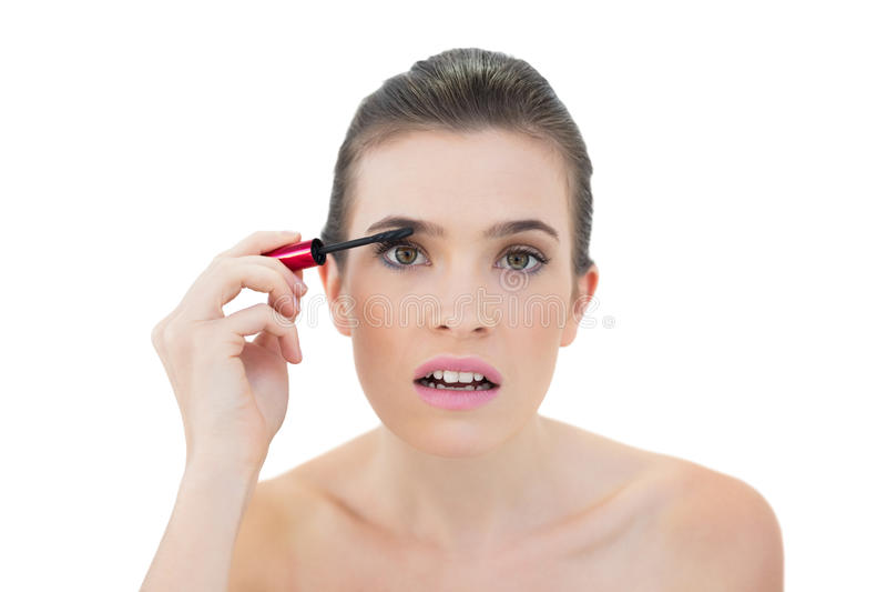 Aandachtig natuurlijk bruin haired model die mascara toepassen stock afbeelding