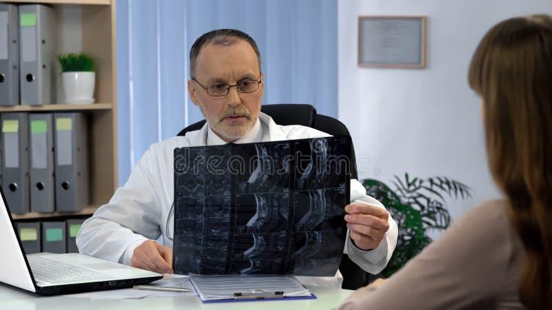 Aandachtige chirurg die halsröntgenstraal bekijken, die bij de diagnose, benoeming werken royalty-vrije stock foto's