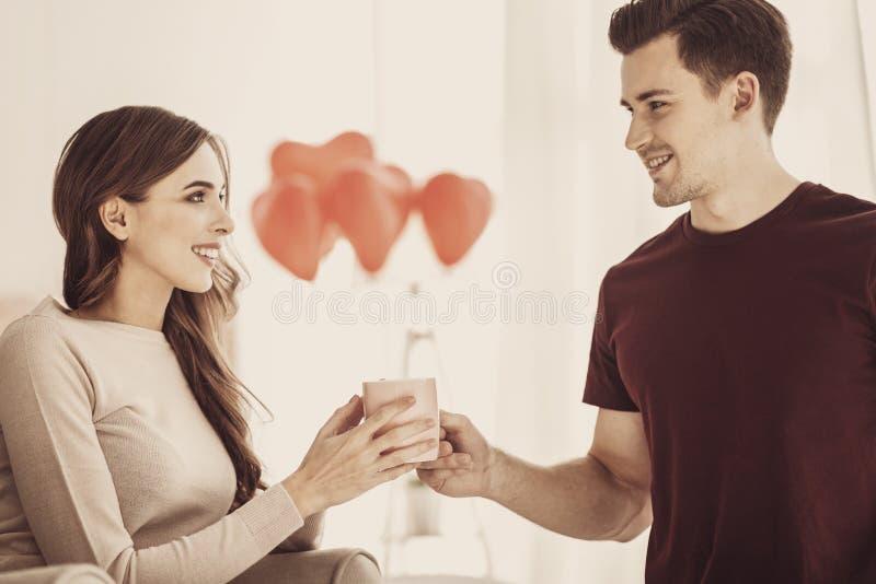 Aandachtige gevende vriend die kop van koffie geven aan zijn fiance royalty-vrije stock afbeeldingen