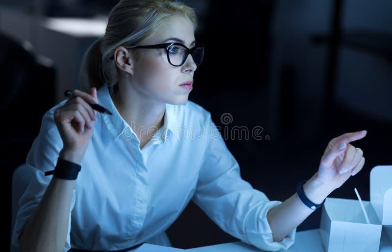 Aandachtige hakker die de orde in het bureau uitvoeren stock foto's