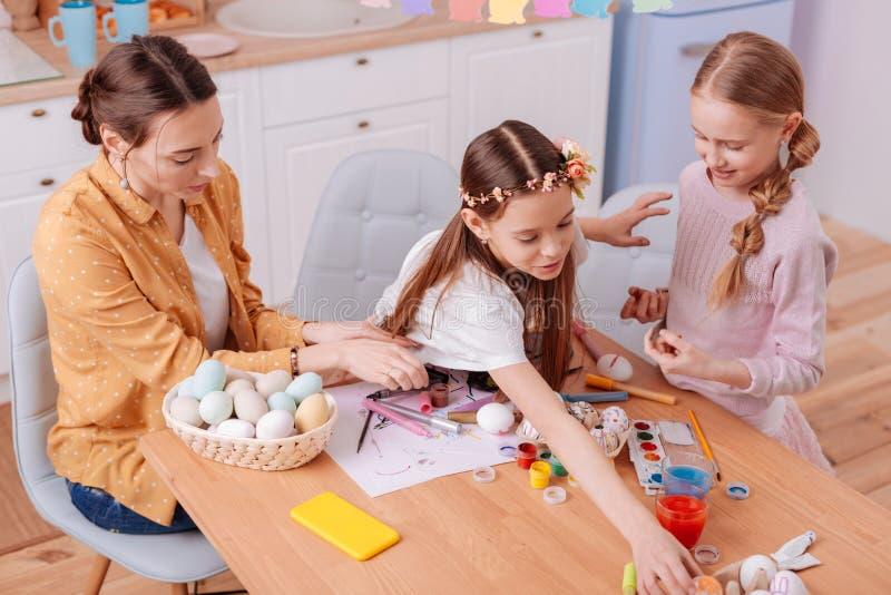 Aandachtige jonge vrouw die haar dochters met het schilderen helpen royalty-vrije stock afbeelding