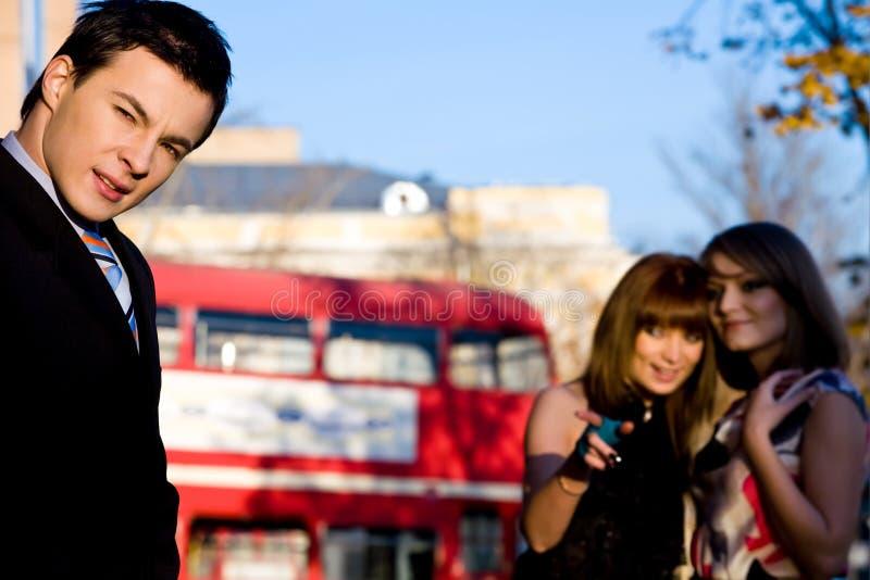 Aandachtige man twee speelse vrouwen in openlucht stock foto