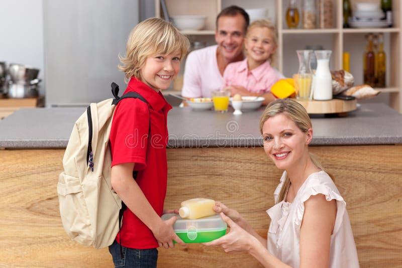 Aandachtige moeder die de schoolmaaltijd inpakt royalty-vrije stock afbeelding